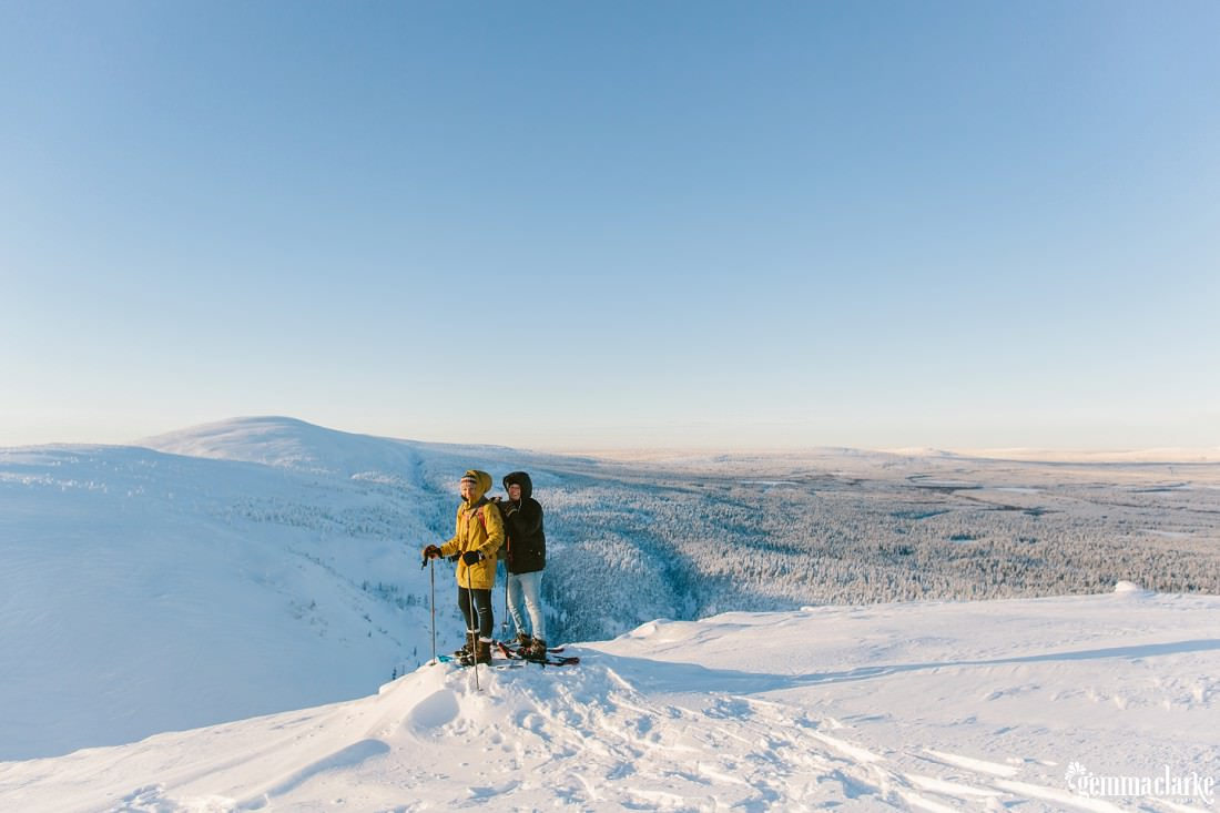 A couple stand together in snow shoes on a hill overlooking a snow covered forest