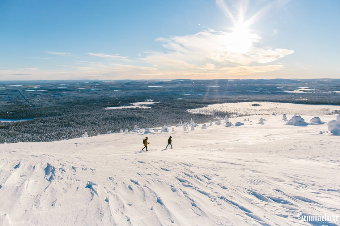 A couple snow-shoeing across a hill overlooking a snow covered forest