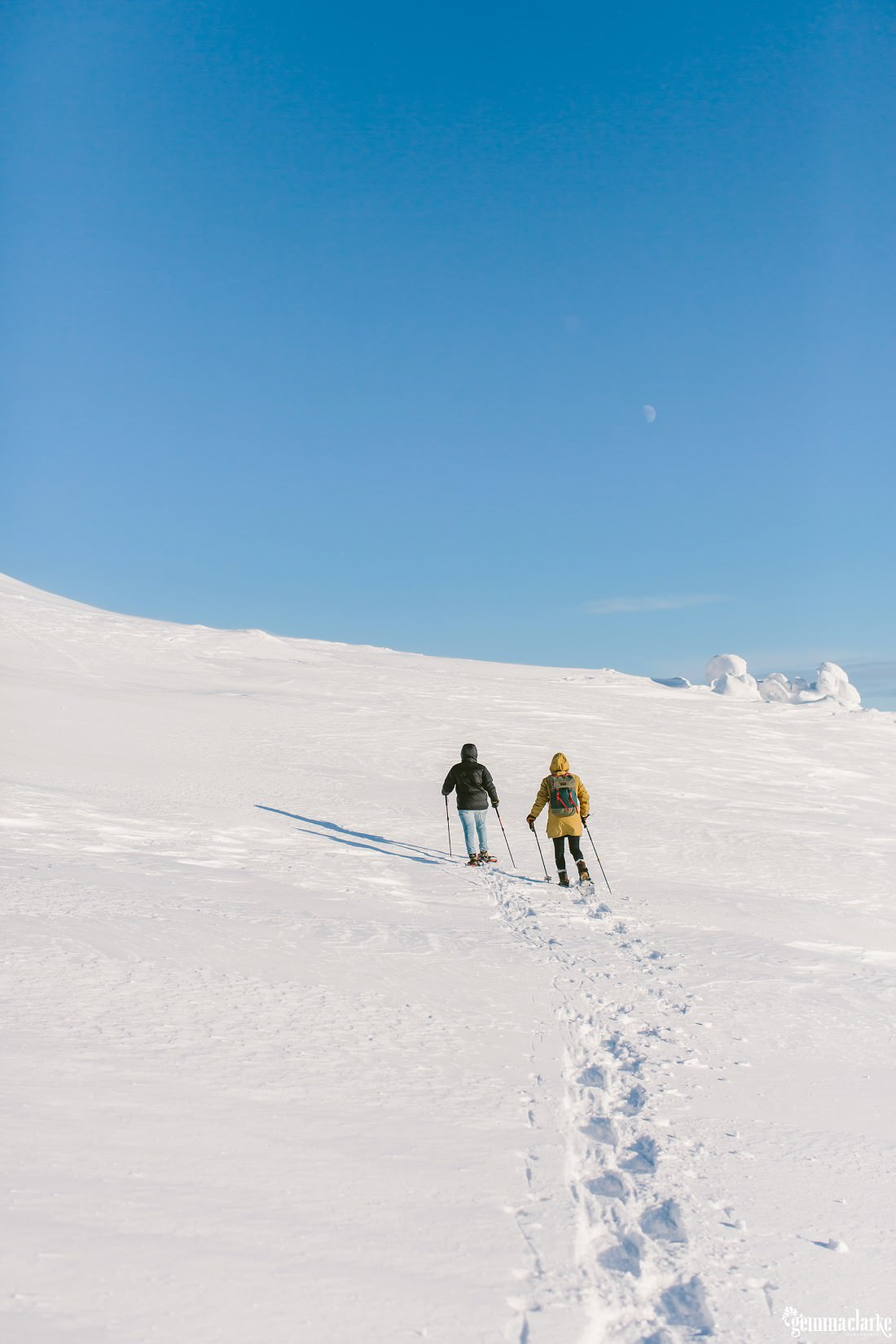 A couple snow-shoeing up a snowy hill