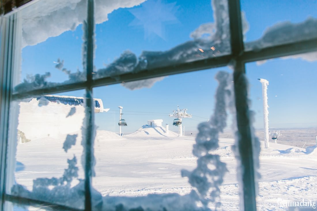 A view through a window of a snow covered ski lift