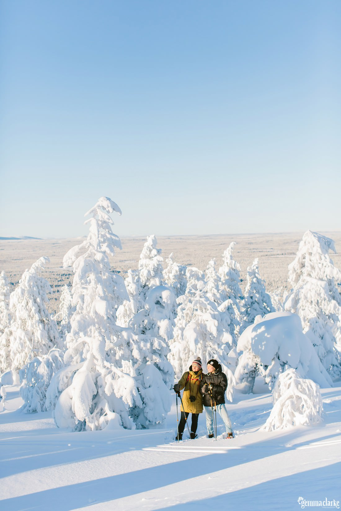 A couple in snow shoes stand in front of trees covered in very thick snow