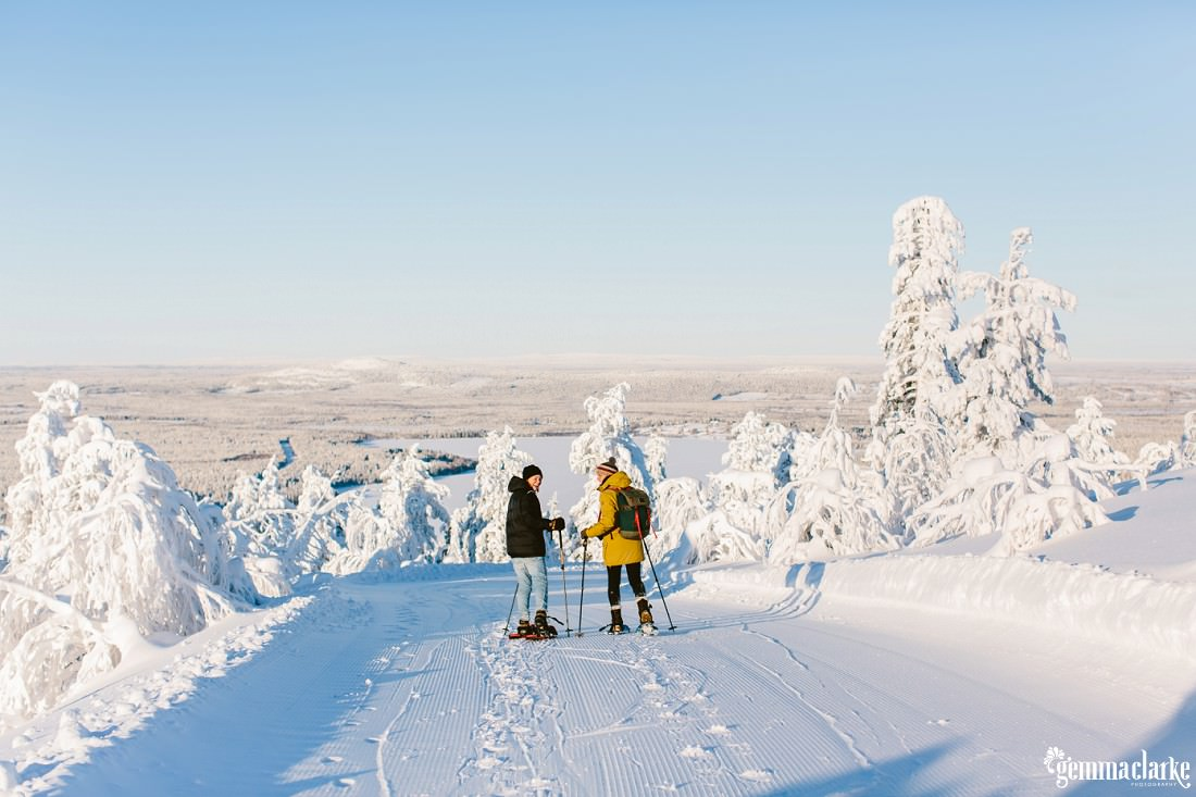 A couple snow-shoeing down a hill towards a snow covered forest