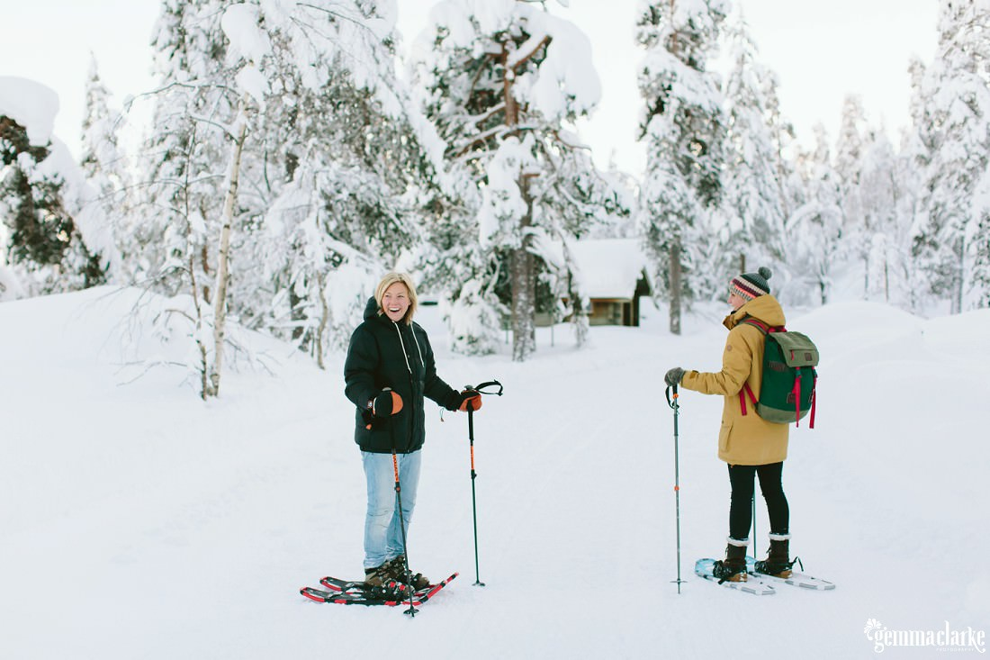 A smiling couple in snow shoes standing near a wooden cabin in a snow covered forest