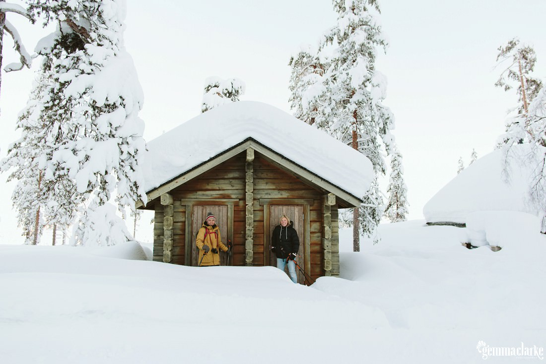 A couple standing in front of a wooden cabin in a forest covered in thick snow