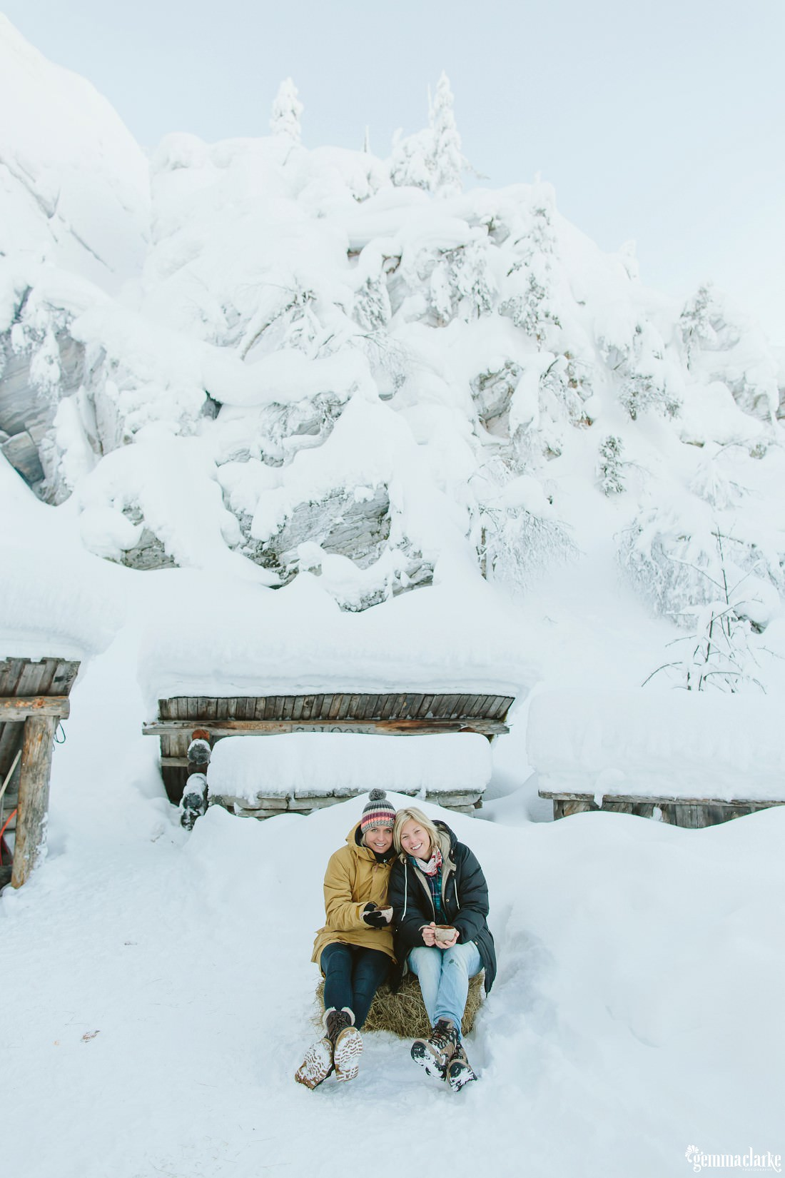 A smiling couple sitting in front of a snow covered cabin