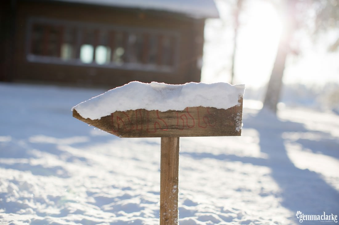 A wooden sign with snow on it