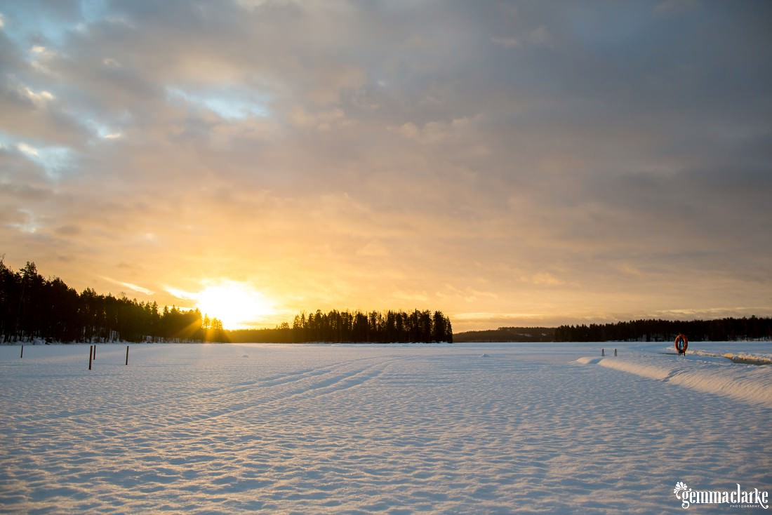 A yellow glowing sunset shines through clouds over a snow covered frozen lake
