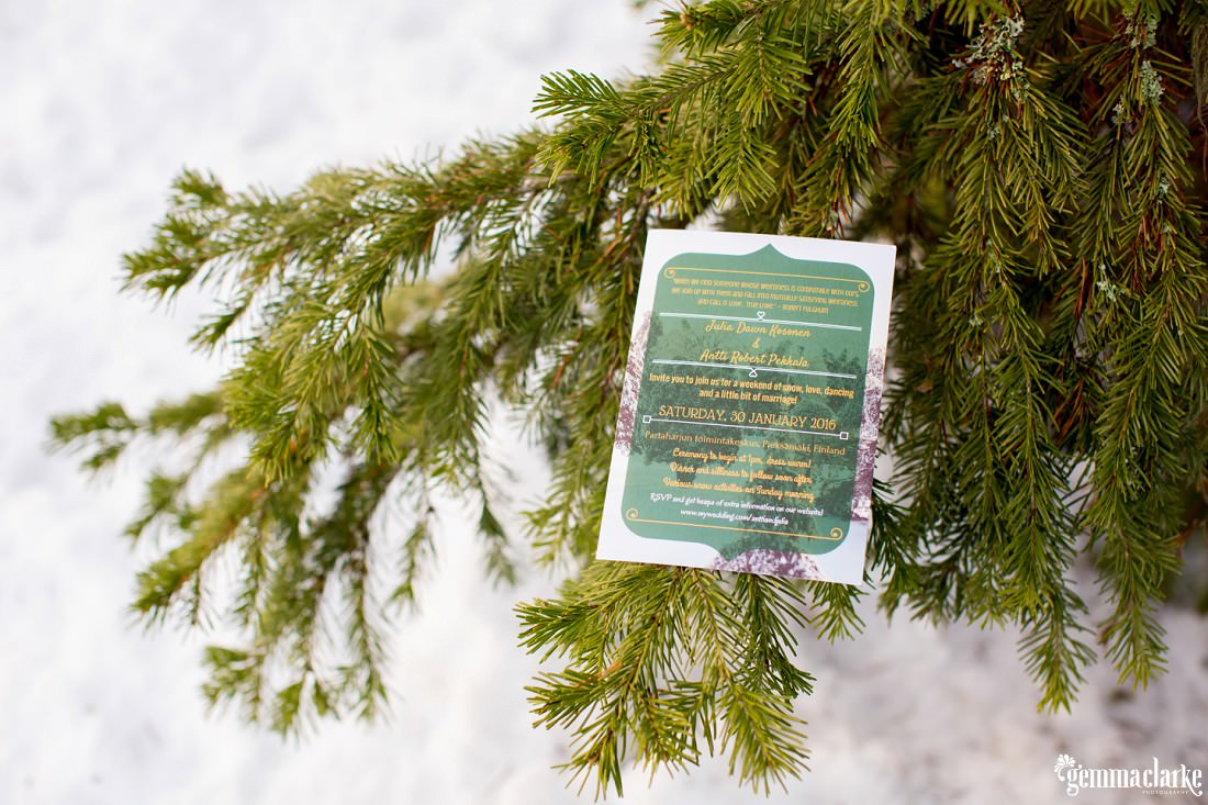 A wedding invitation that has been placed on the branch of a pine tree with a snowy background