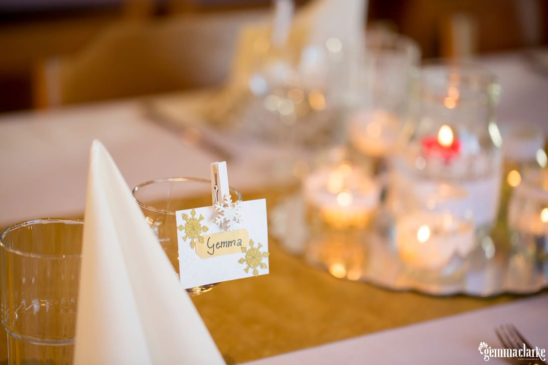 A table setting at a wedding reception with a name tag pegged to a glass