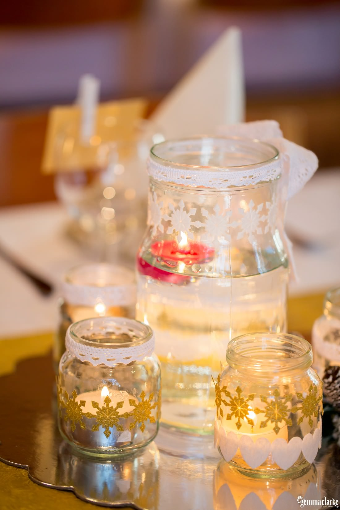 Tealight candles floating in water in jars