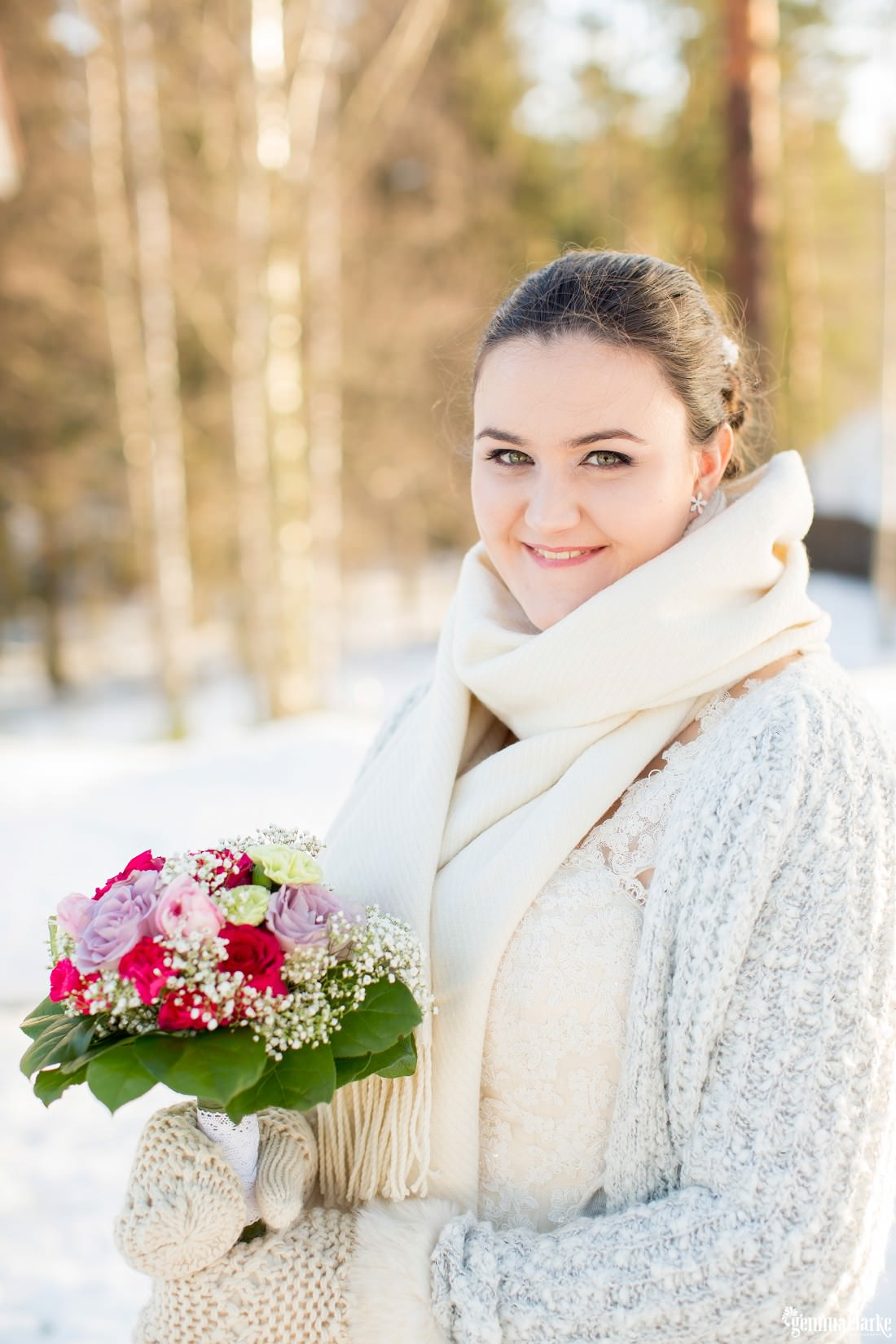 A bride in a white gown with scarf and mittens stands in the snow holding a floral bouquet