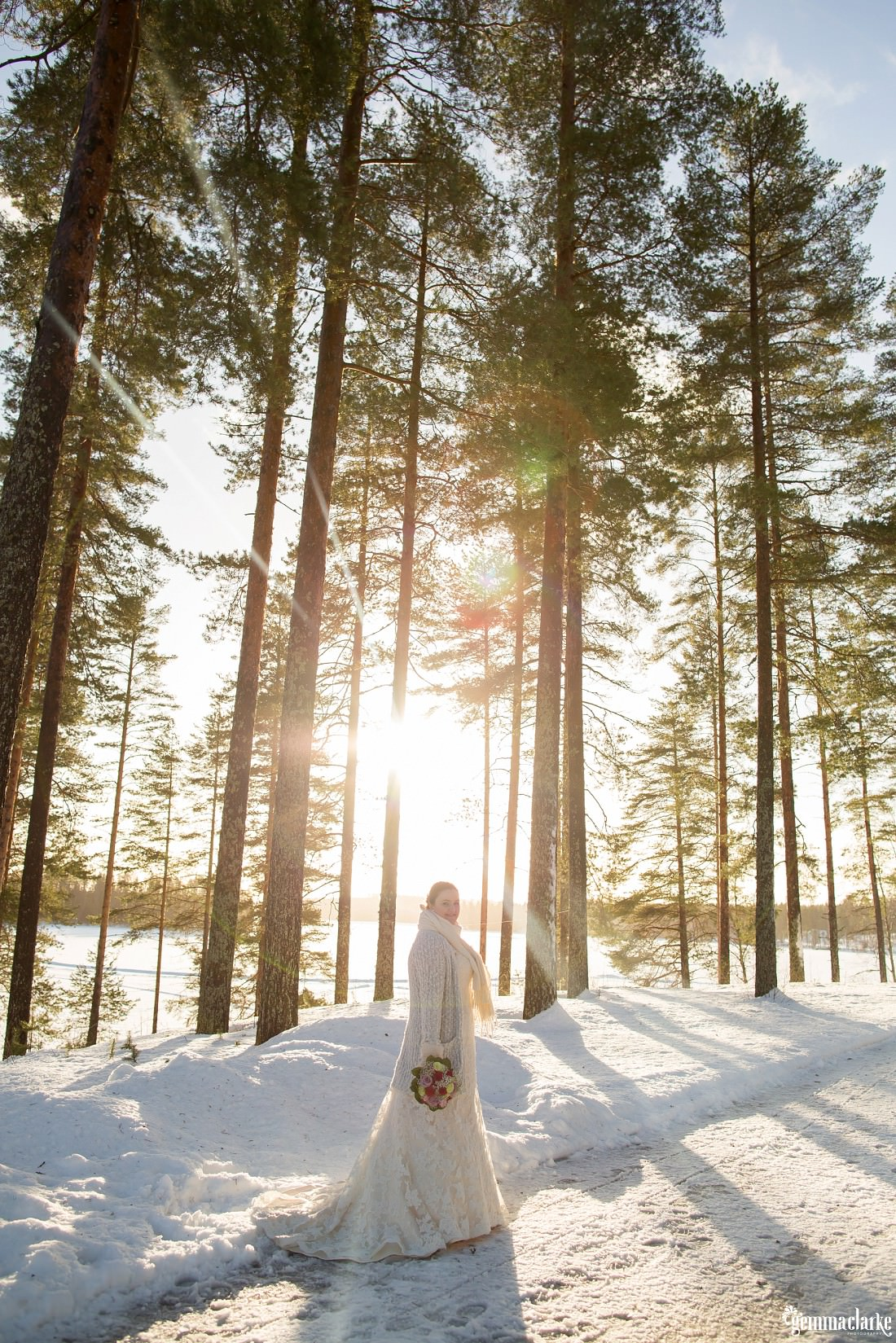 A bride in a white gown with scarf and mittens stands in the snow holding a floral bouquet as sunlight streams through the trees behind her