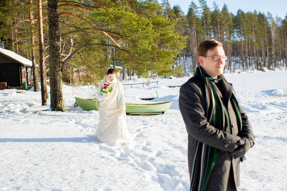 Groom stands looking away with a smile as his bride walks towards him from behind through the snow