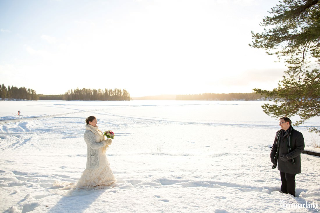 A bride and groom get their first look of each other on their wedding day in front of a snow covered frozen lake