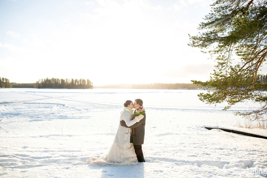 A bride and groom share a kiss in front of a snow covered frozen lake