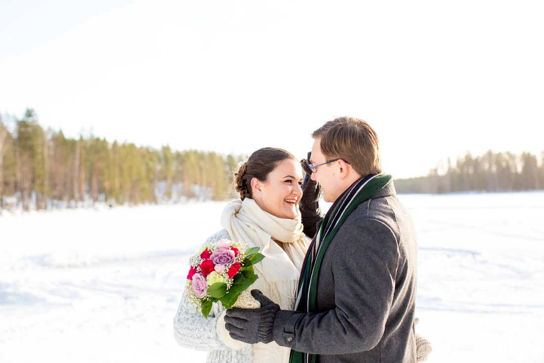 A groom brushes a hair away from his bride's face as they smile at each other while standing in the snow