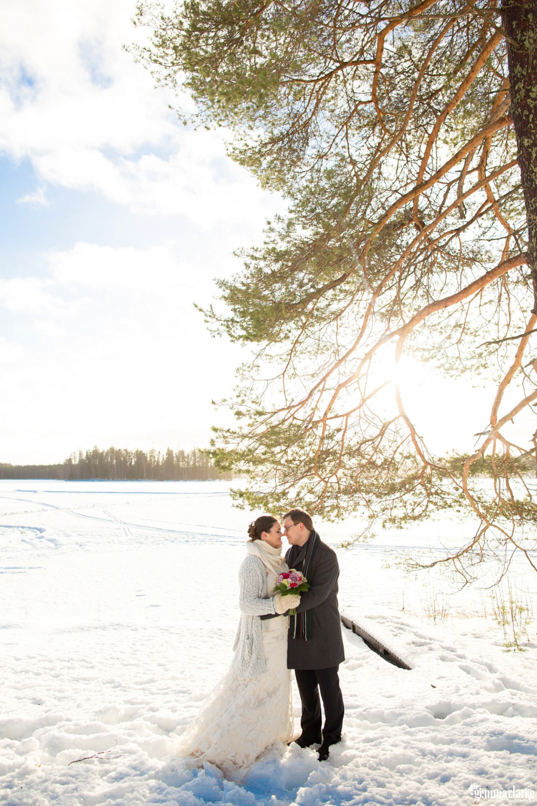A bride and groom share an eskimo kiss as they stand in front of a snow covered frozen lake