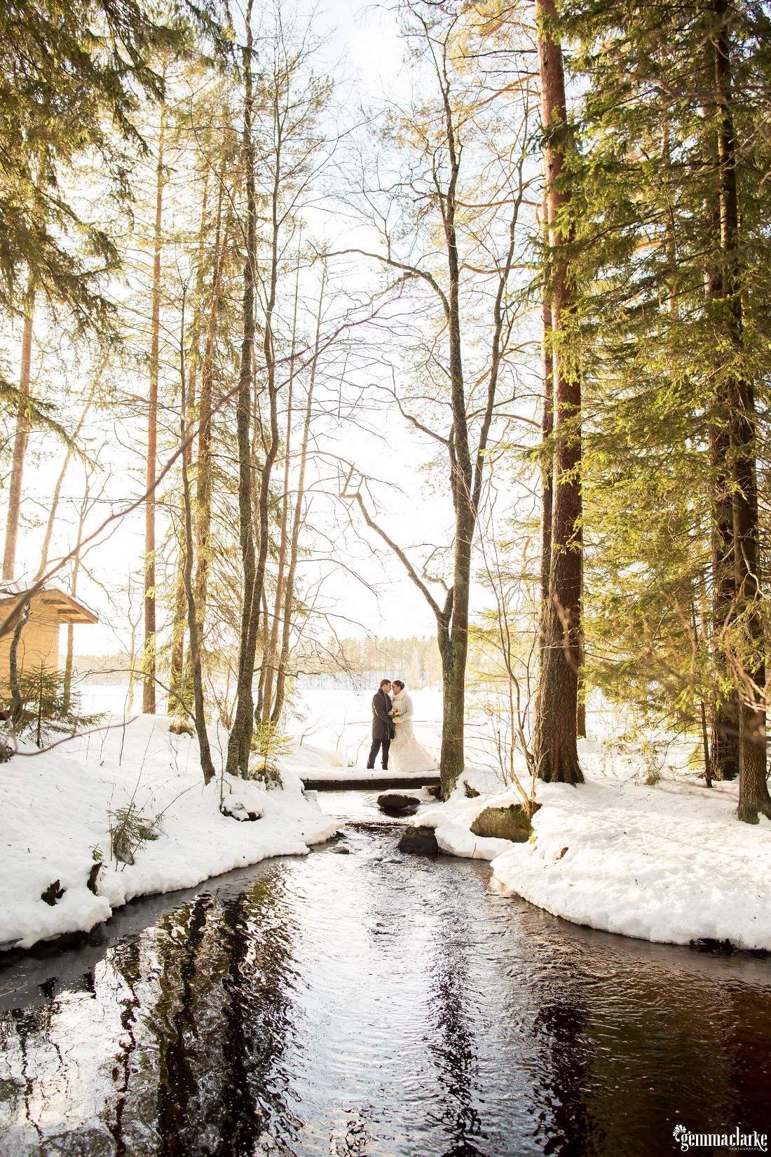 A bride and groom stand on a bridge over a small river in a snowy forest