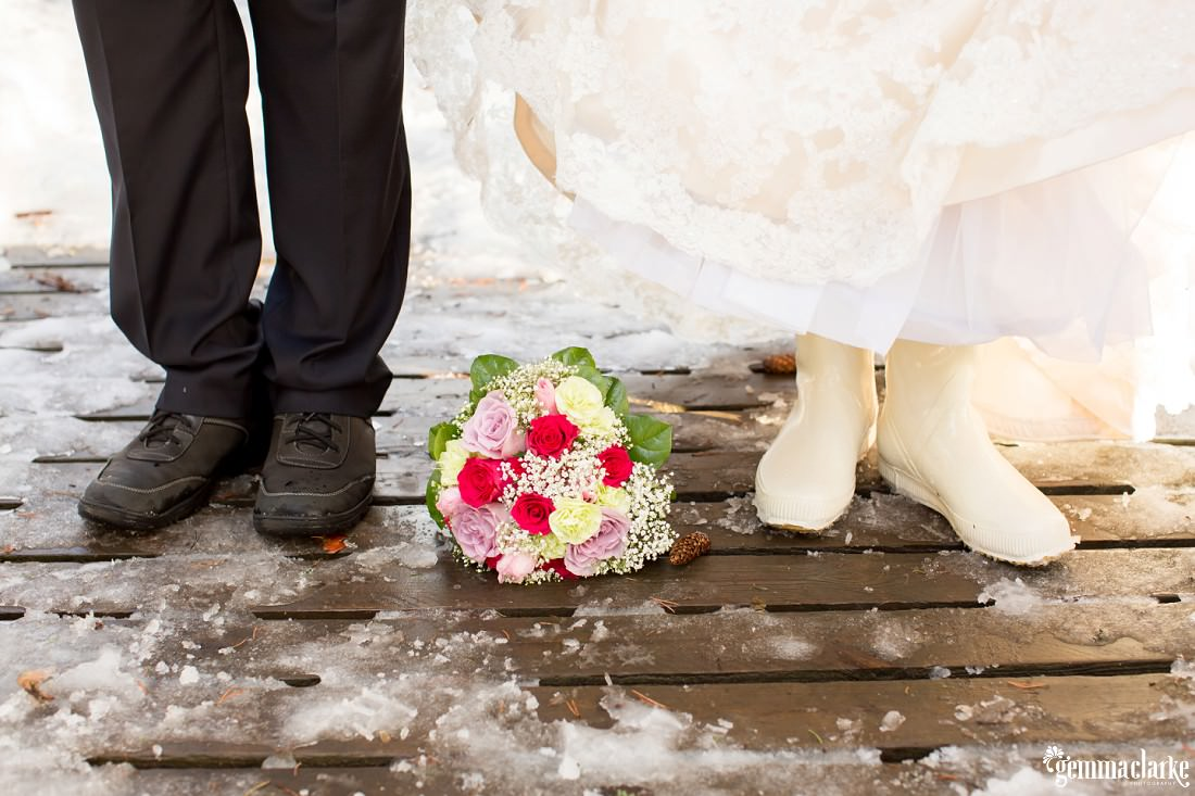 A bride and groom stand either side of a floral bouquet on a small wooden bridge
