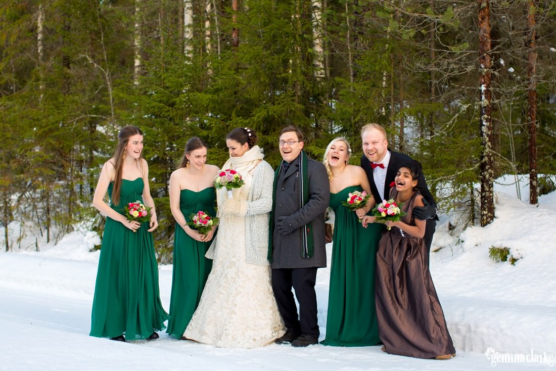 A smiling bridal party standing together in the snow
