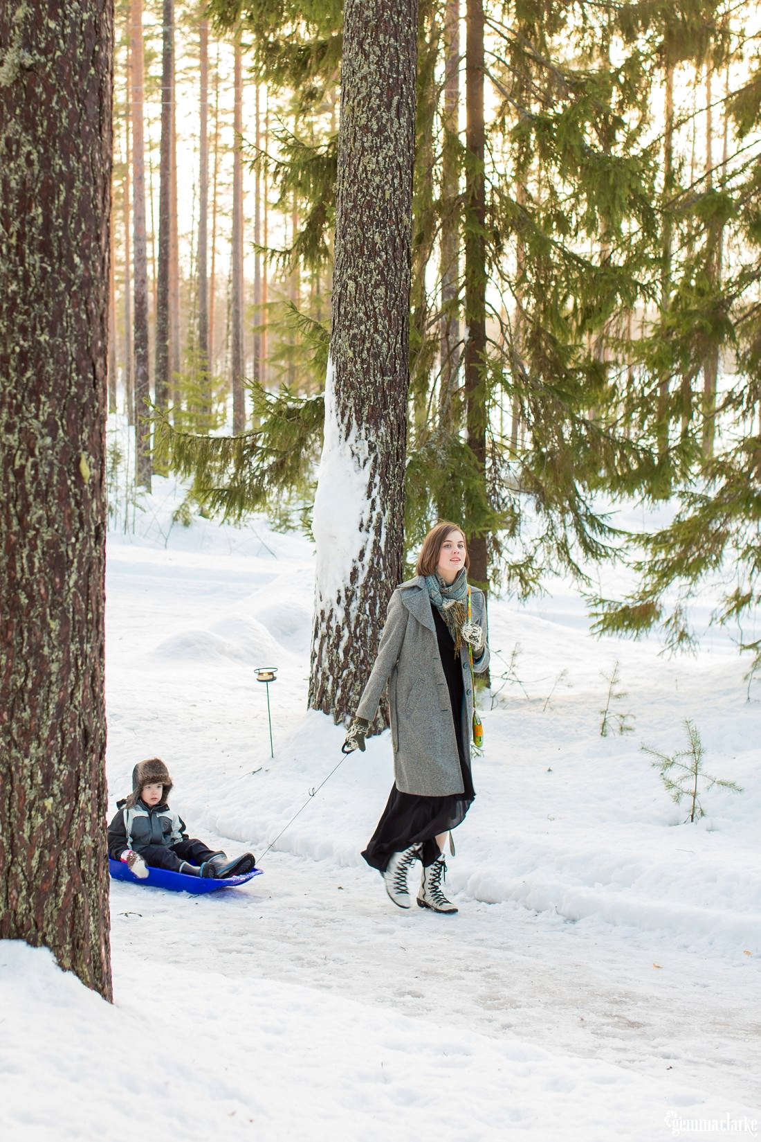A woman pulling a young boy through snowy forest in a plastic toboggan