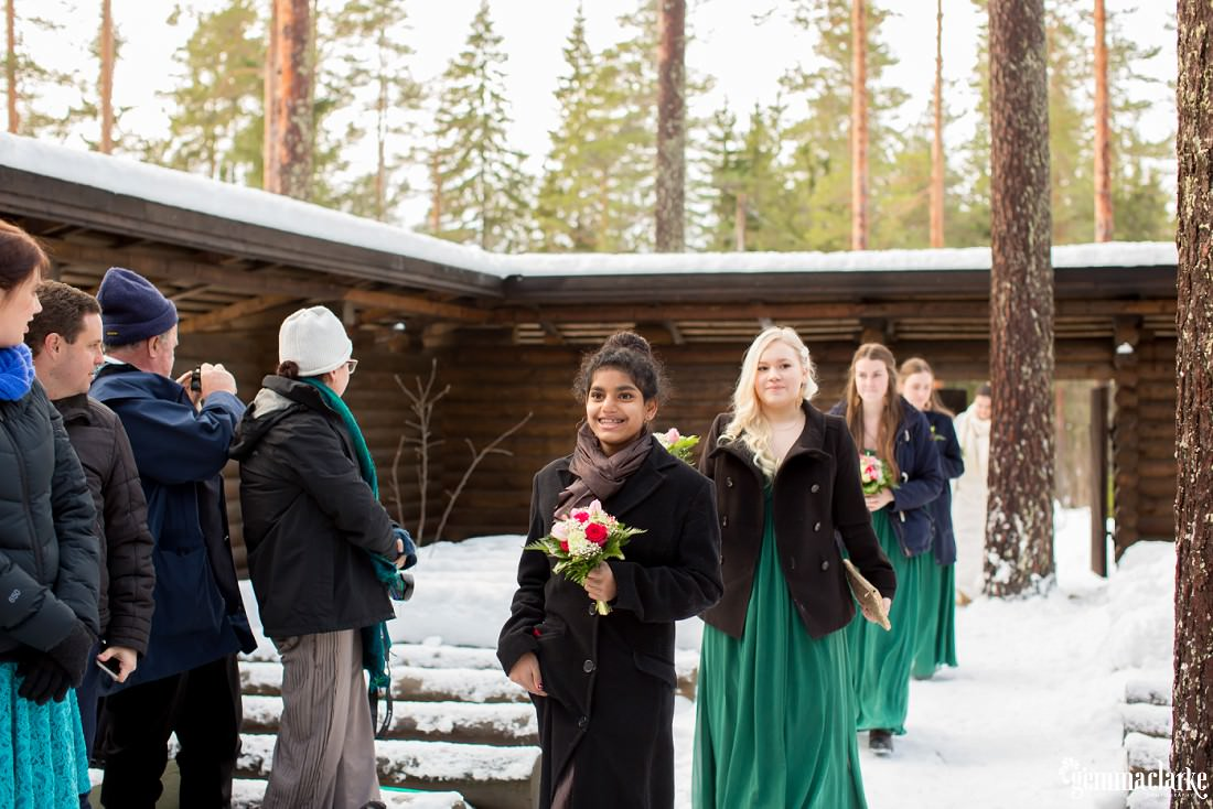 A flower girl and bridesmaids walk down the aisle of a snowy outdoor chapel
