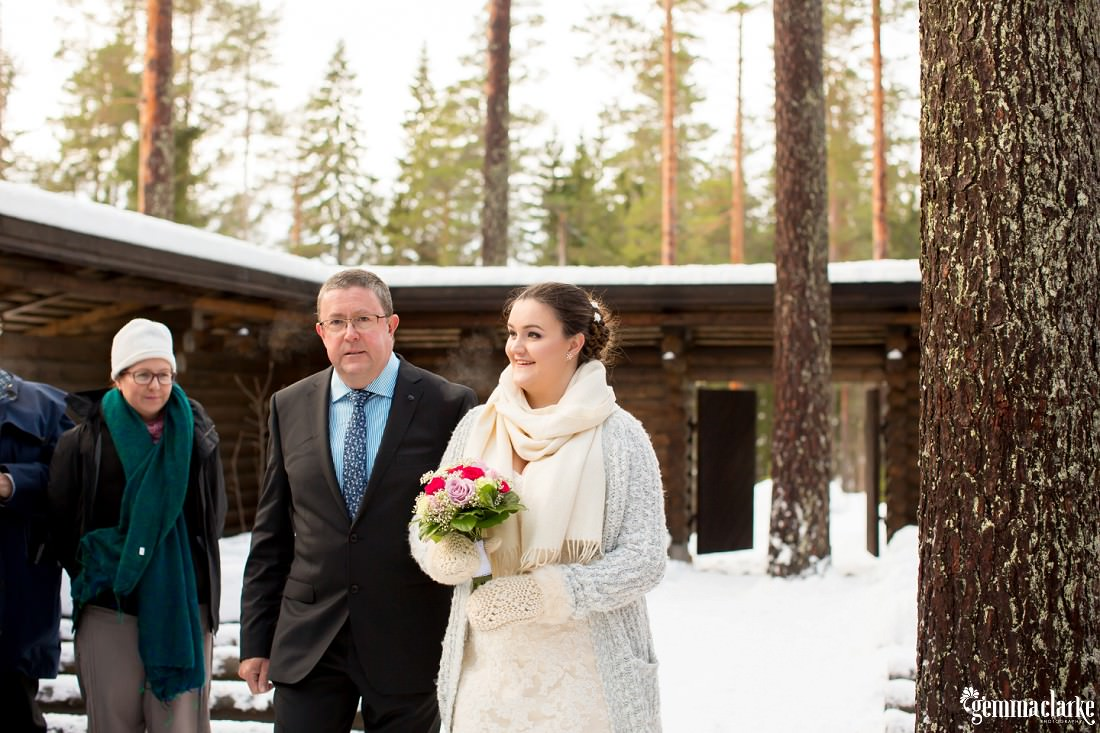 A bride being walked down the aisle of a snowy outdoor chapel by her father