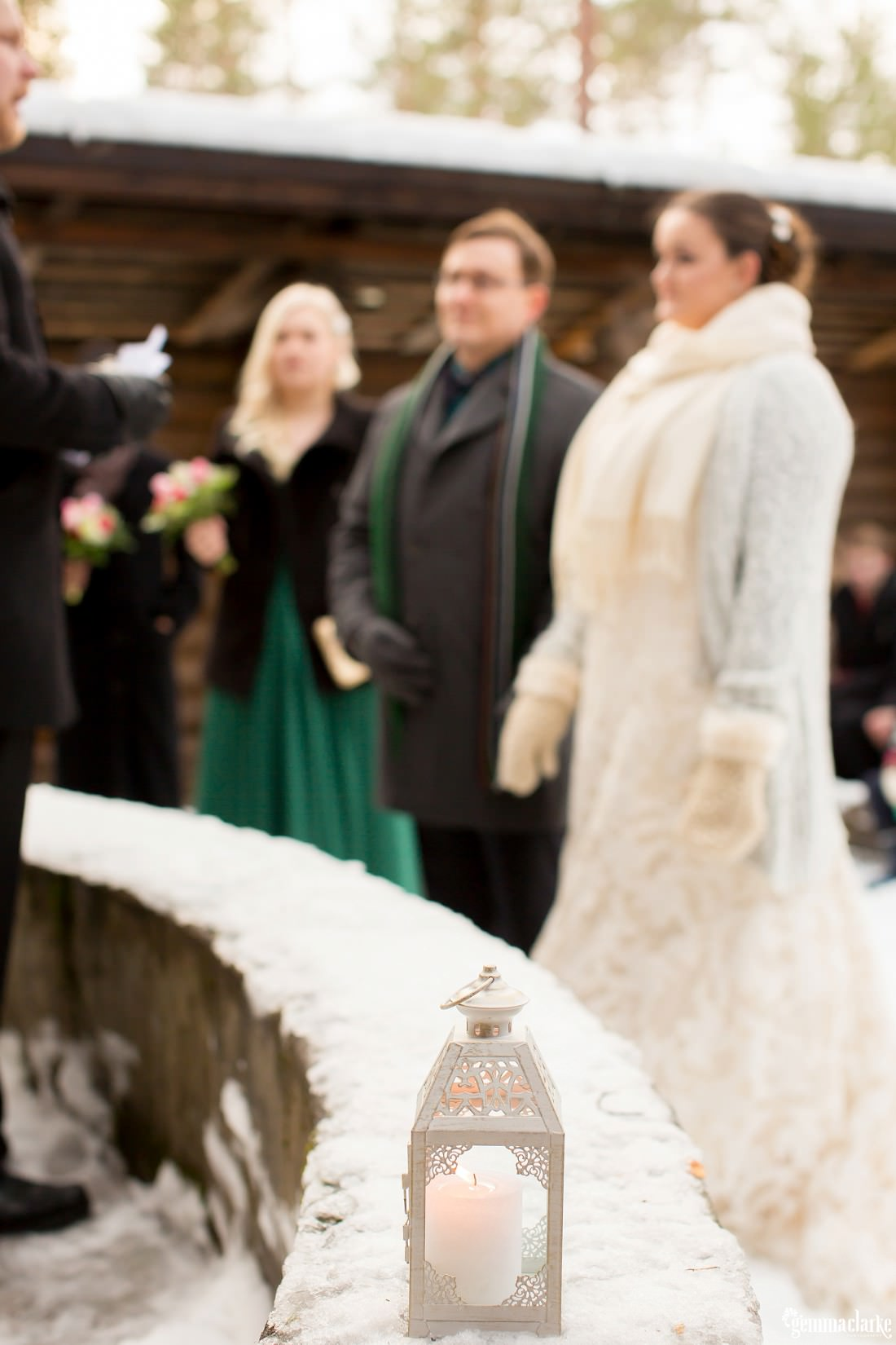 A lantern on a snowy ledge in the foreground with a bride and groom in the background