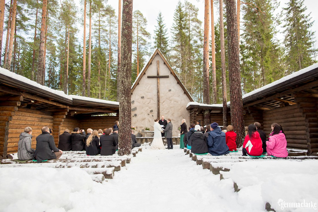 Wedding guests look on as a bride and groom are married in a snowy open air chapel