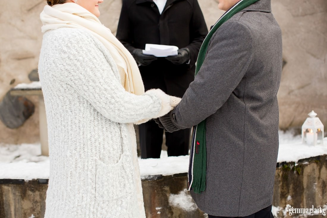 A bride and groom hold hands at their wedding ceremony in a snowy open air chapel