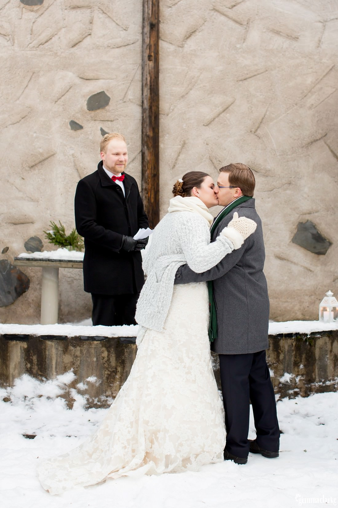 A wedding celebrant smiles as the bride and groom share a kiss at their wedding ceremony