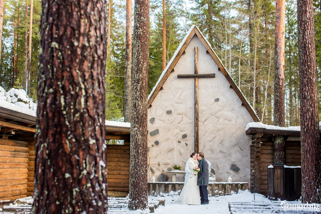 A bride and groom share a kiss while standing in a snowy open air chapel