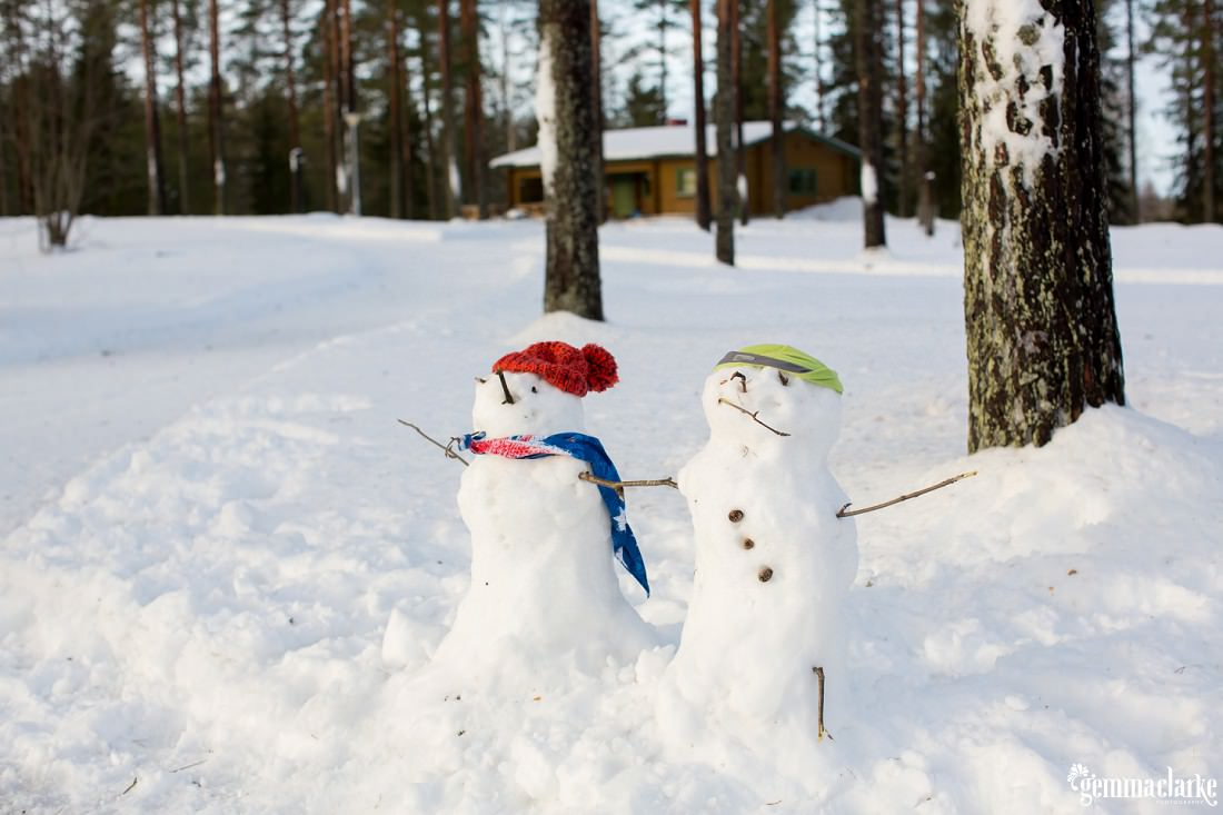 Two snowmen in a forest, one with Finnish decoration and one with an Australian flag (representing the bride and groom)