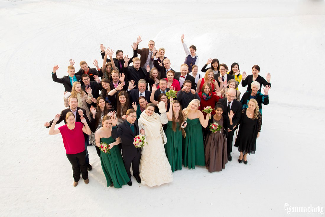 A shot from above of wedding guests smiling and waving while standing in the snow