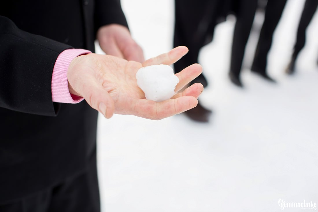 A closeup of a snow ball in a man's hand