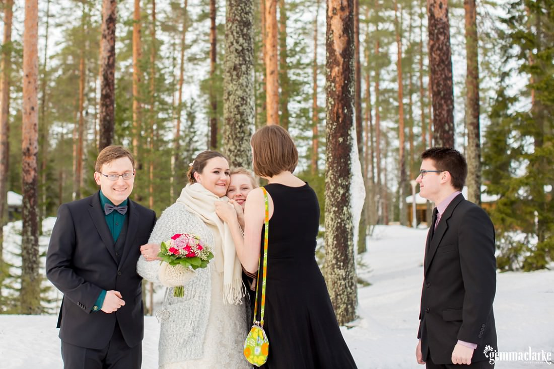 A bride and groom are congratulated by guests