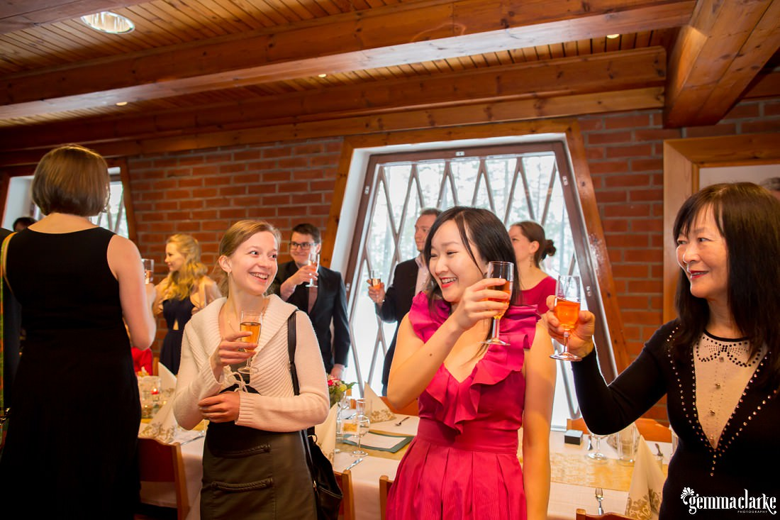 Smiling wedding guests raise their glasses