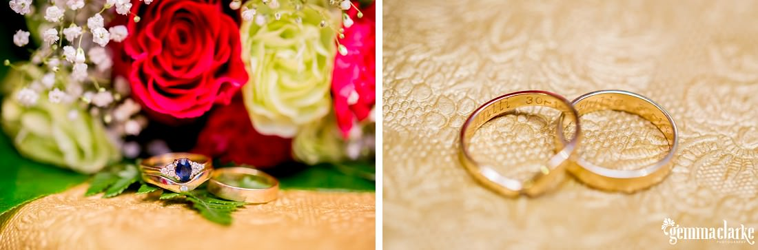 A bride and groom's rings on a table in front of some flowers