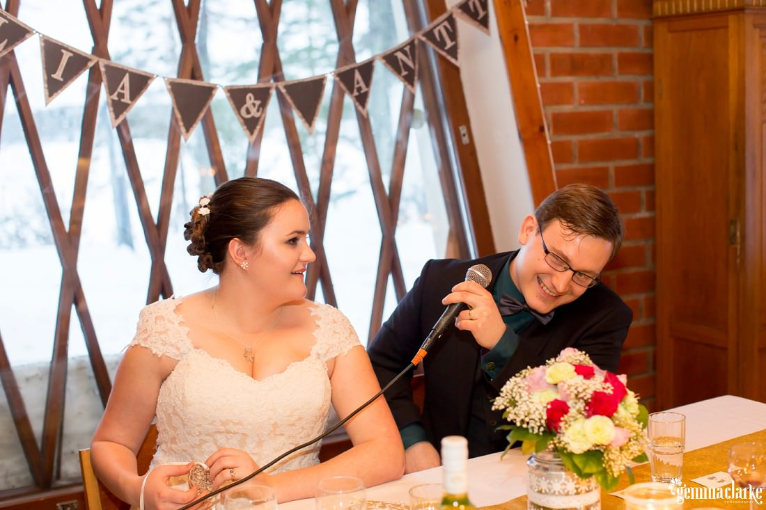 A bride smiles at her groom as he speaks into a microphone