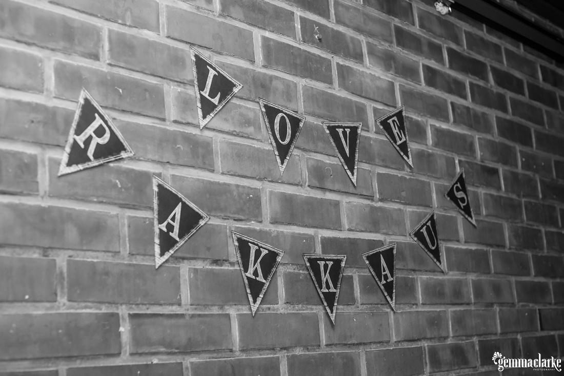 "Bunting that says ""love"" in English and Finnish against a brick wall"