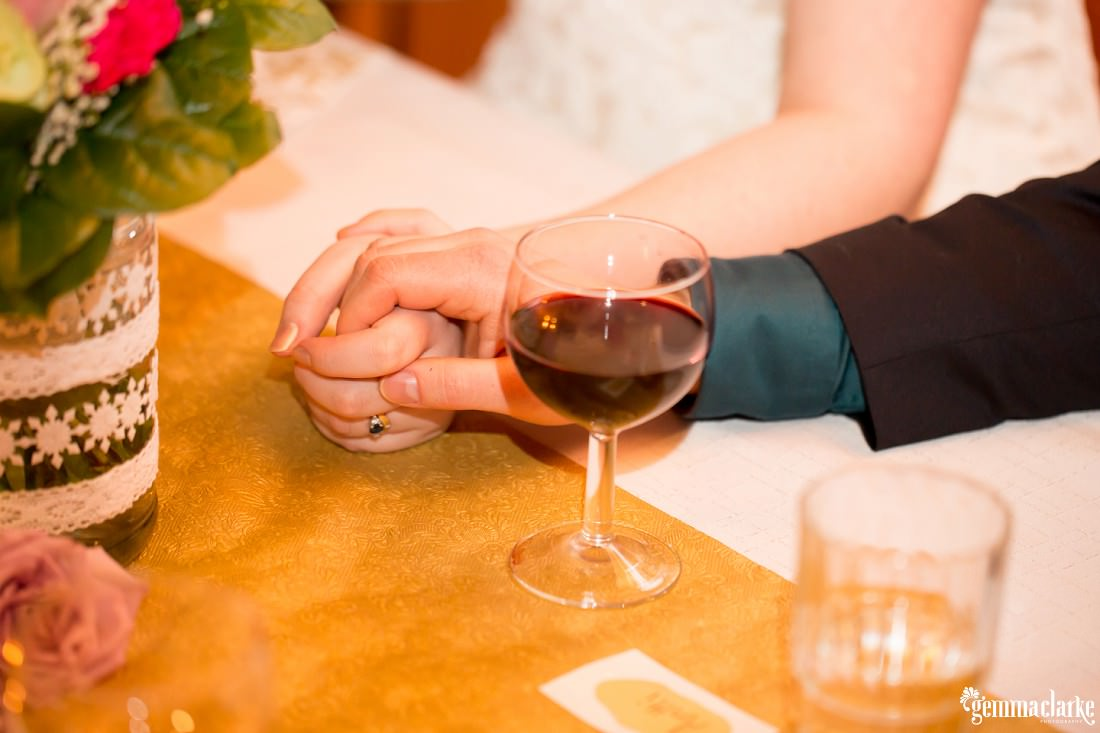 A bride and groom hold hands at their bridal table