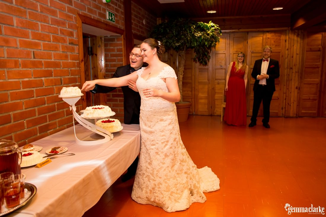 A smiling bride and groom cut their wedding cake
