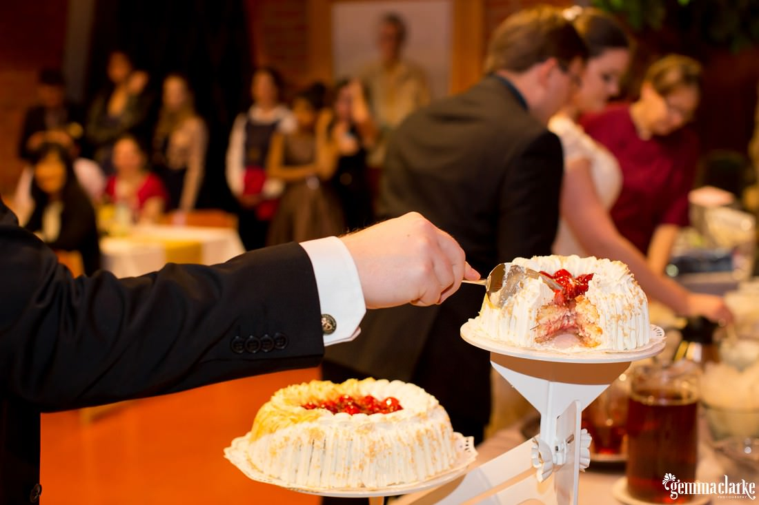 A man slices himself a piece of wedding cake