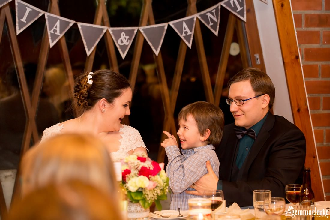 A young boy smiles and points at the bride as the groom watches