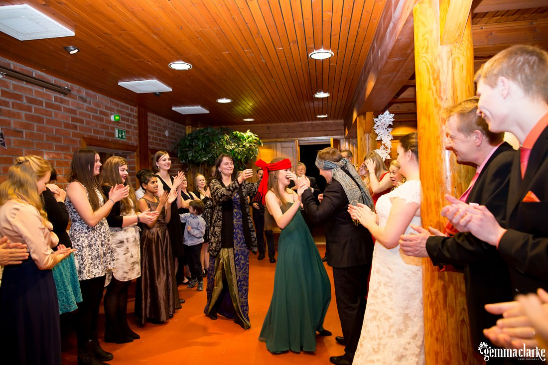 Wedding guests play a game as others clap their hands