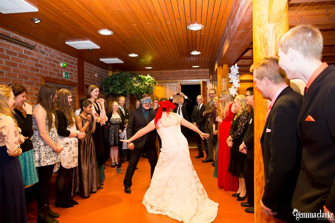 A blindfolded bride and groom play a game as their guests look on