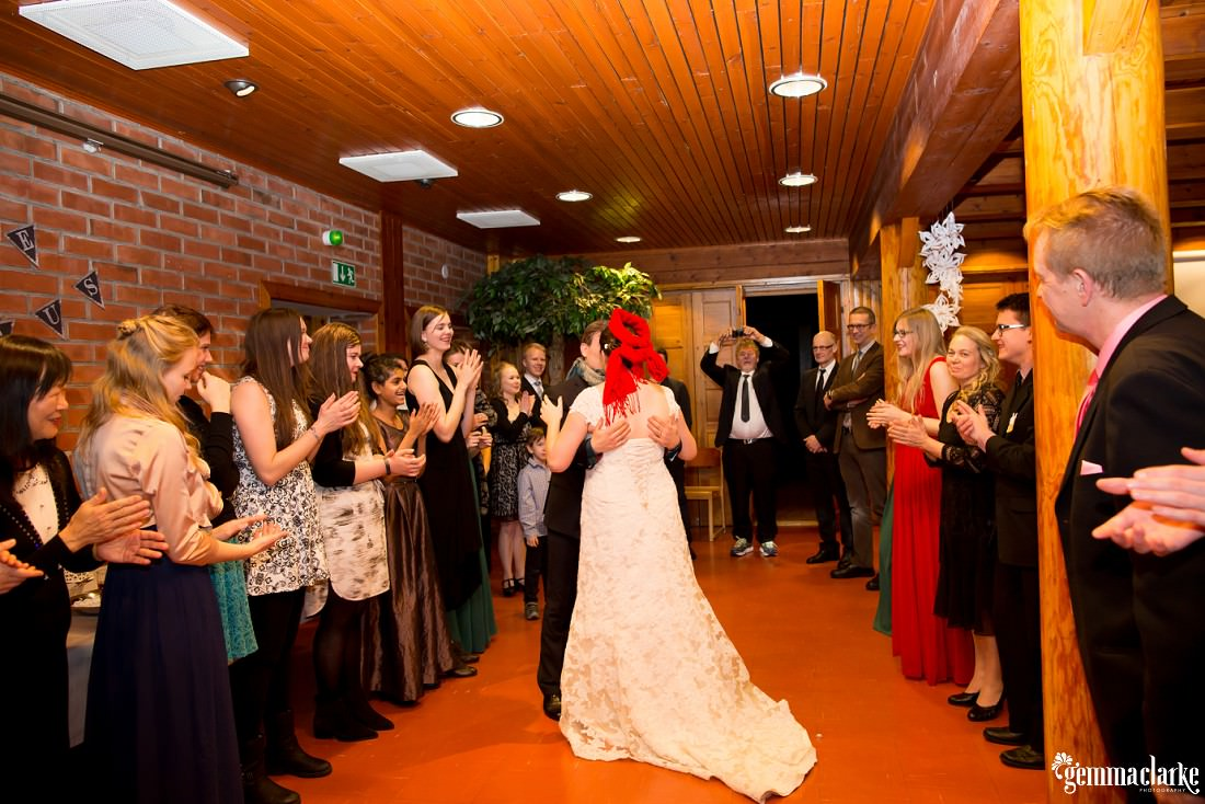 A bride and groom share a kiss at their wedding reception as their guests clap their hands