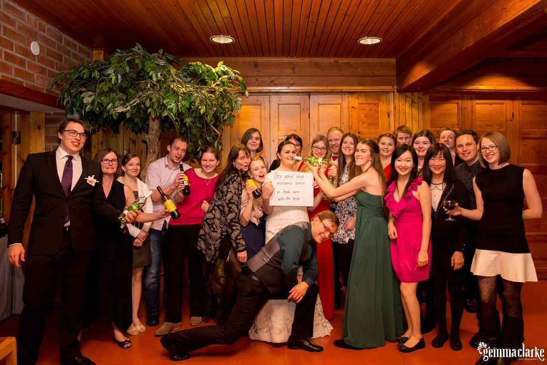"Wedding guests stand with the bride and groom as the bride holds a sign that says ""I've drank wine with the bride"""