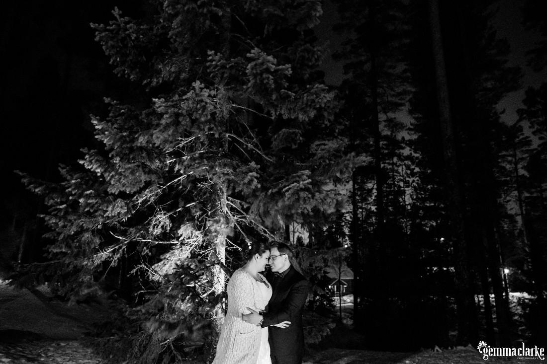 A bride and groom embrace in front of a lit tree at night