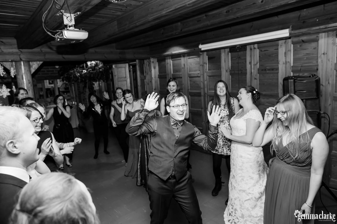 A groom dances as his bride and wedding guests watch on